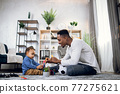 Afro american father playing with cute son on carpet 77275621