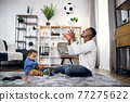 Happy father and son sitting on carpet and playing with ball 77275622