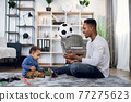 Happy father and son sitting on carpet and playing with ball 77275623