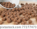 Crispy chocolate cereal flakes scattered on a wooden cutting kitchen board. Macro. Sweet breakfast idea for kids 77277473