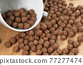 Chocolate cereal balls are scattered over the board with a white teacup. Round flakes. Close-up 77277474