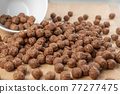 Crunchy chocolate cereal. Textured flakes balls. Macro 77277475