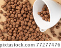 Chocolate cereal balls are scattered over the board with a white teacup. Close-up 77277476