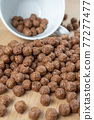 Chocolate cereal balls are scattered over the board with a white teacup. Close-up 77277477