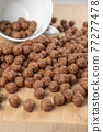 Crunchy chocolate cereal with white cup. Textured flakes balls. Macro 77277478