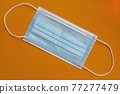 New medical protective surgical mask on a bright orange background. Close-up 77277479