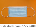 One medical surgical protective face mask close up on orange colorful background 77277480