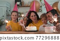 birthday. happy family on holiday party. parents fun and childs with baby getting ready to blow out birthday cake with candles. happy family at birthday. baby blows out the candles on cake 77296888