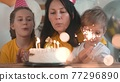 birthday. happy family on holiday party. parents and childs with baby getting ready to blow out birthday cake with candles. fun happy family at birthday. baby blows out the candles on cake 77296890