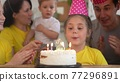 birthday. happy family on holiday party. parents and kids with baby getting ready to blow out birthday cake with candles. happy fun family at birthday. baby blows out the candles on the cake 77296891
