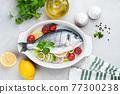 Dorado fish in ceramic dish ready for cooking 77300238