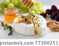 Honey pouring on camembert cheese 77300251