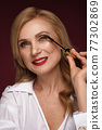 Portrait of a beautiful elderly woman in a white shirt with classic makeup and blond hair. 77302869