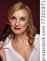 Portrait of a beautiful elderly woman in a white shirt with classic makeup and blond hair. 77302871