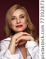 Portrait of a beautiful elderly woman in a white shirt with classic makeup and blond hair. 77302873
