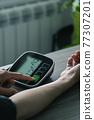 man measures his blood pressure 77307201