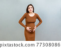 a pregnant girl who has a stomach ache stands on a colored background. isolated 77308086