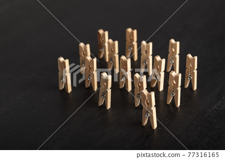 Set of wooden clothespins stand on black background. People group meeting concept. 77316165