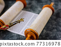 Reading a Torah scroll during a bar mitzvah ceremony . 77316978