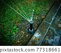 Automatic watering system in the park working. Sprinkler in park diagonal view 77318661