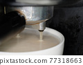 coffee preparation. Coffee is pouring in cup 77318663