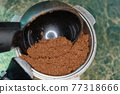 Adding Ground coffee in portafilter with plastic spoon macro image 77318666