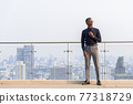 Full length shot of handsome African businessman outdoors at rooftop thinking 77318729