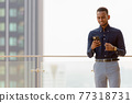 Portrait of handsome African businessman outdoors at rooftop 77318731