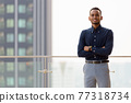 Portrait of handsome African businessman outdoors at rooftop with arms crossed 77318734