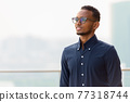 African businessman outdoors at rooftop smiling and thinking 77318744