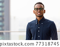 Portrait of handsome African businessman smiling outdoors at rooftop 77318745