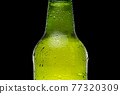 Green beer bottle on black background. Drops on the bottle. Cold and refreshing beer 77320309