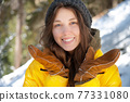 Attractive young caucasian woman in a winter yellow down jacket and a knitted hat smiling looks at the camera against the background of a snowy coniferous forest on a sunny day 77331080