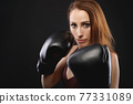 Portrait Caucasian fitness girl in boxing gloves stands in a rack on a black background, portrait of a strong and independent woman fighter 77331089