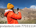 young caucasian woman taking pictures on her smartphone while in the mountains 77331114