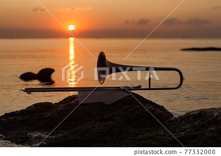 wind instrument pipe lies near the sea on a stone on the background of the red dawn 77332008
