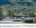 A perfect neighbourhood. Office building on mountain slope background 77345050