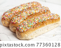 Iced finger buns with sprinkles 77360128