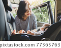 Asian Mother helping her little baby boy son to fasten belt on his car seat 77365763