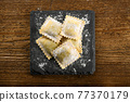 Uncooked ravioli pasta on board with flour 77370179