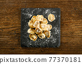 Raw cappelletti pasta on board with flour 77370181