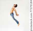 Fit man with bare chest leaping on white background 77370184