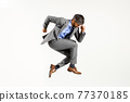Businessman in smart suit jumping in midair on white 77370185