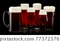 Set of fresh draft beer glasses with bubble froth isolated on black background. 77372376