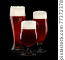 Set of fresh stout beer glasses with bubble froth isolated on black background. 77372378