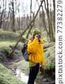 Woman in hiking clothes with camera in forest 77382279