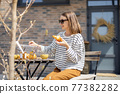 Cheerful woman sitting at a table in the garden. 77382282
