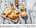 Croissants under the glass cloche with cups of coffee 77382285