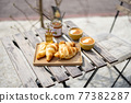Croissants under the glass cloche with cups of coffee 77382287