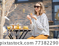 Cheerful woman sitting at a table in the garden. 77382290
